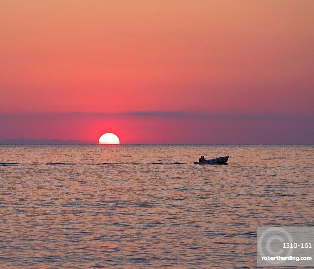 View across the Tyrrhenian Sea at sunrise, small boat crossing Calura Bay, Cefalu, Palermo, Sicily, Italy