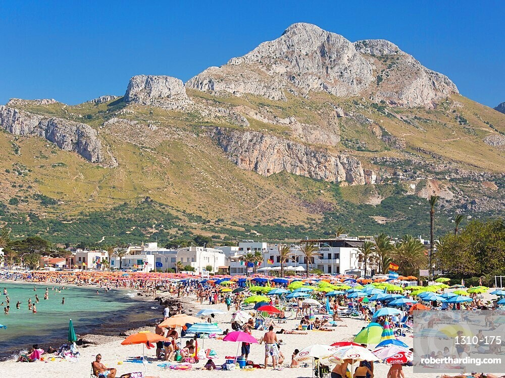 View across colourful crowded beach to the rugged slopes of Pizzo di Sella, San Vito Lo Capo, Trapani, Sicily, Italy