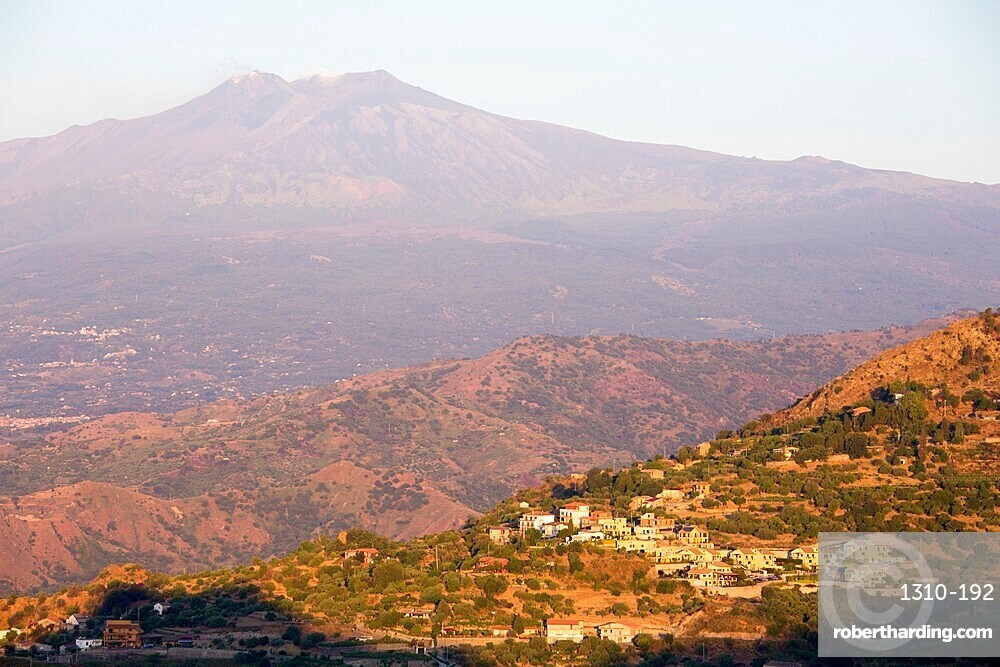 View across rolling volcanic landscape to the summit of Mount Etna, sunrise, Taormina, Messina, Sicily, Italy
