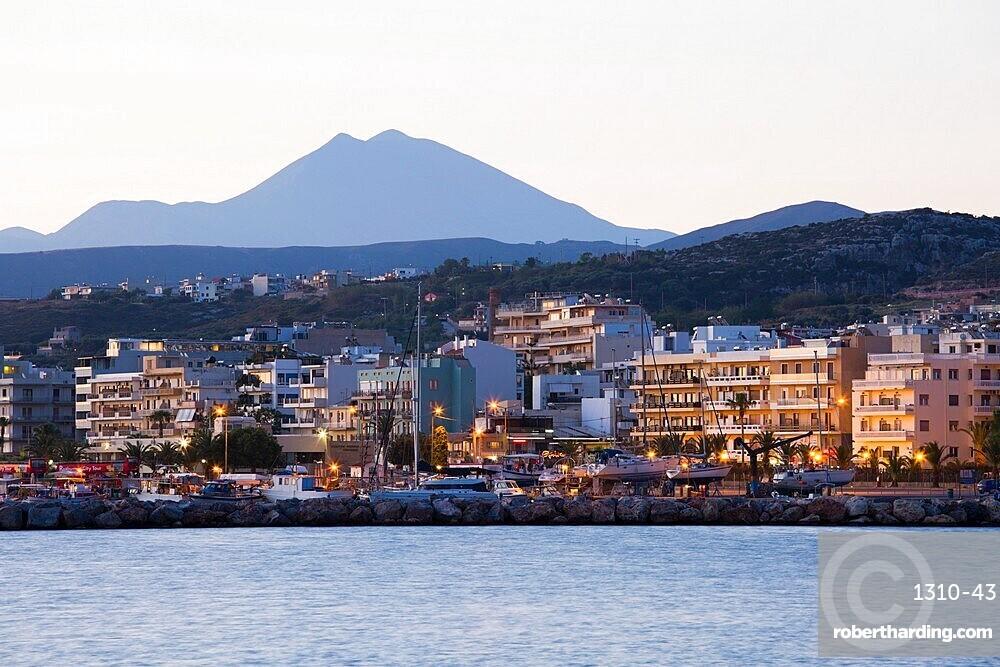 Seafront buildings illuminated at dawn, Mount Psiloritis, aka Mount Ida, in background, Rethymno (Rethymnon), Crete, Greek Islands, Greece, Europe
