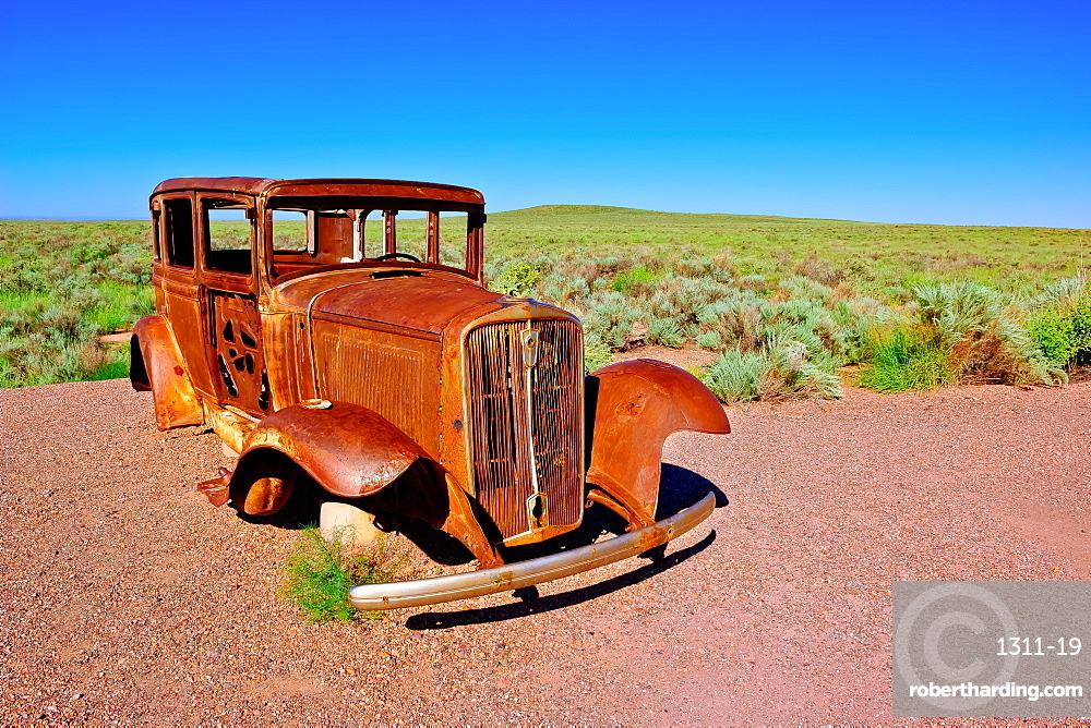 The old rusting steel shell of a Model-T mounted on concrete pillars along the old historic Route 66 in Arizona.