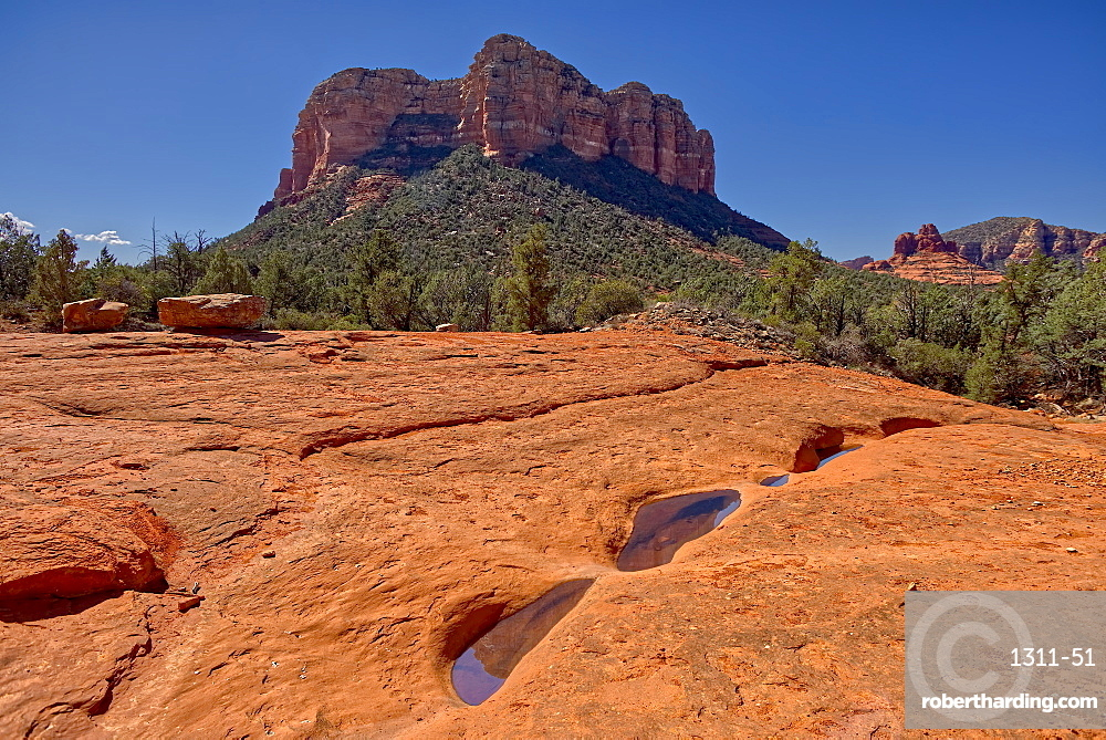 Reflections of Courthouse Butte in the Slick Rock Bowls along the Llama Trail in Sedona AZ.