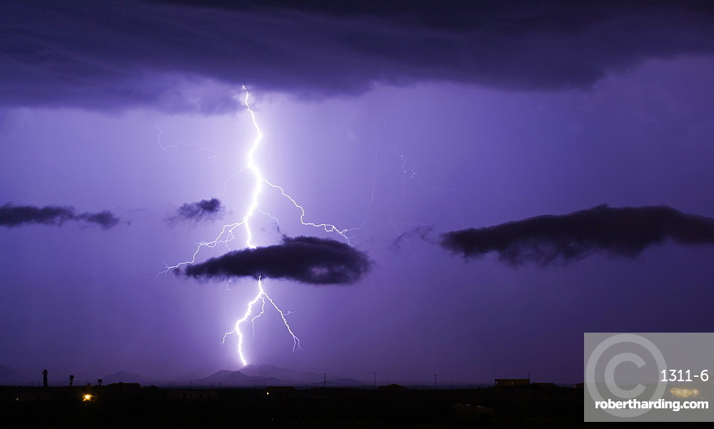 A bright lightning bolt passing through a cloud and striking in the Gila Bend Mountains south of Arlington, Arizona, United States of America, North America
