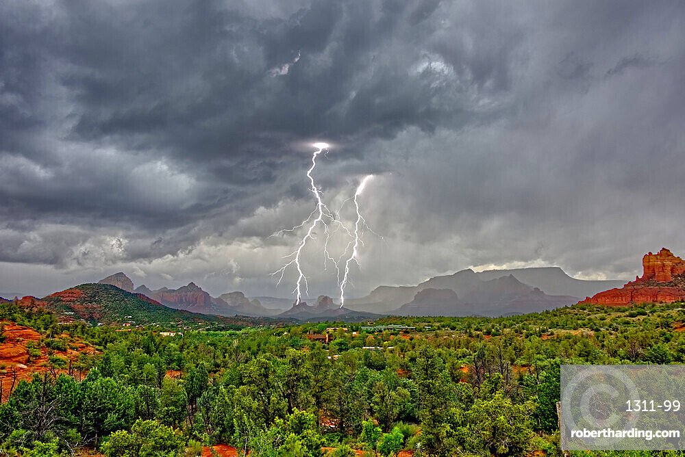 Lightning striking during a storm over Cibola Rock in Uptown Sedona Arizona. Viewed from the Broken Arrow Trail.