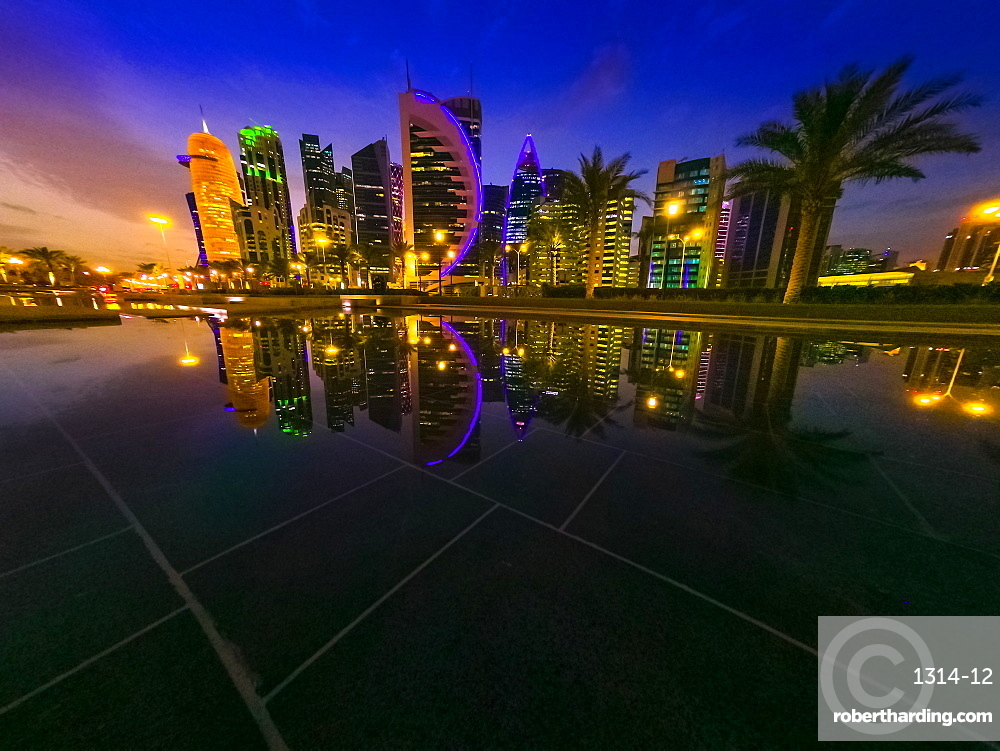Skyline illuminated of Doha in Qatar. Scenic cityscape of West Bay skyline at evening reflecting at downtown park.