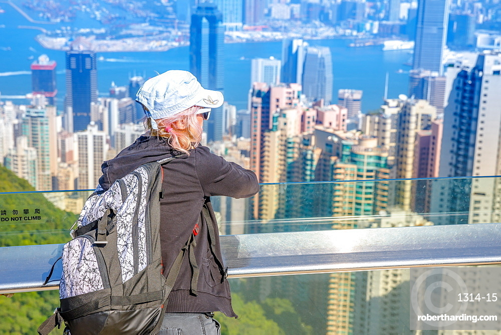 Traveler freedom asia concept. Hong Kong Victoria Peak tourist looking the view on Victoria Harbour from Peak Tower. Defocused background.