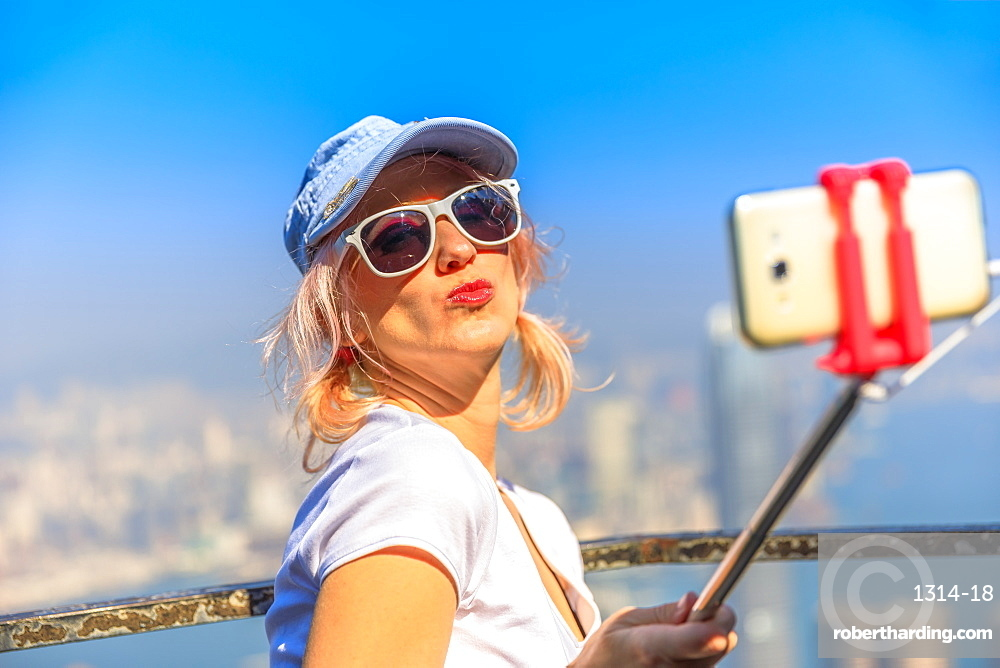 Traveler freedom asia concept. Hong Kong Victoria Peak tourist taking selfie stick picture photo with smartphone enjoying view over Victoria Harbour from viewing platform on top of Peak Tower.