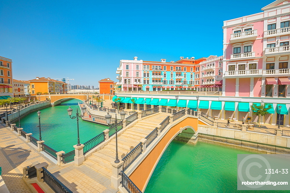 Two bridges in Venice Doha at Qanat Quartier in the Pearl, Persian Gulf, Middle East in a sunny day. Aerial view picturesque and luxurious district icon of Doha, Qatar in venetian style.