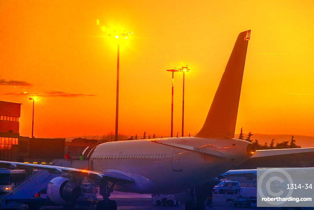 Commercial airplane parked in airport park at sunset. Orange red sky and copy space. Backlit sunset time. Refueling in taxi mode