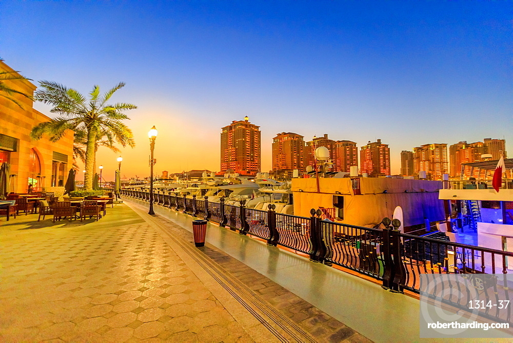 Marina corniche promenade at night in Porto Arabia at the Pearl-Qatar, Doha, with residential towers and luxury boats and yachts in Persian Gulf, Middle East.