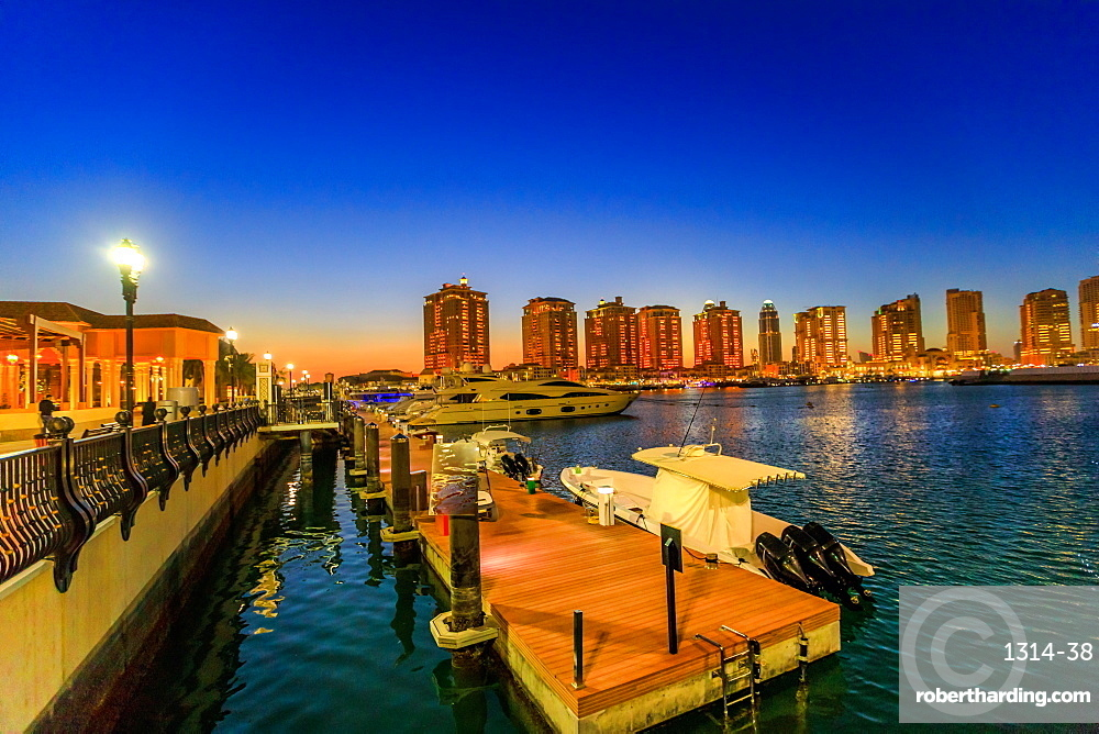 Luxurious yachts and boats docked at Porto Arabia Marina at night. The Pearl-Qatar in Doha is an artificial island icon of the city and a popular tourist destination in Persian Gulf, Middle East.