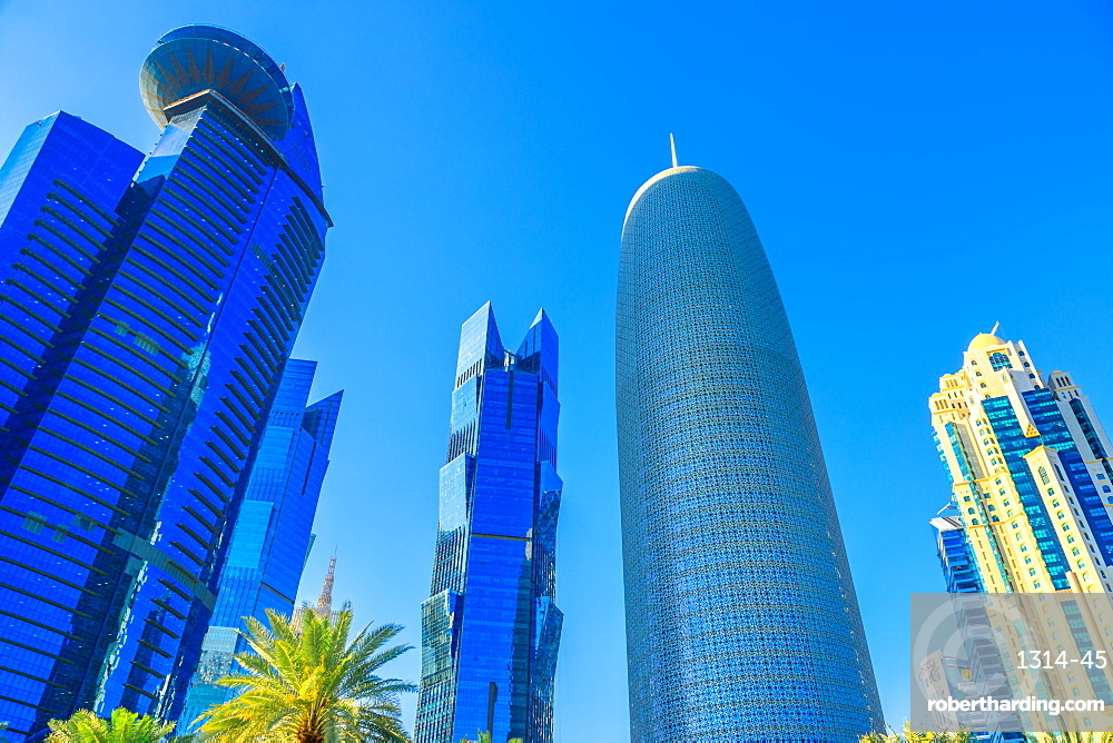 Doha, Qatar - February 17, 2019: bottom view of Woqod Tower and Alfardan Towers in West Bay area. Modern glassed skyscrapers in Doha Downtown, Middle East. Urban scene.