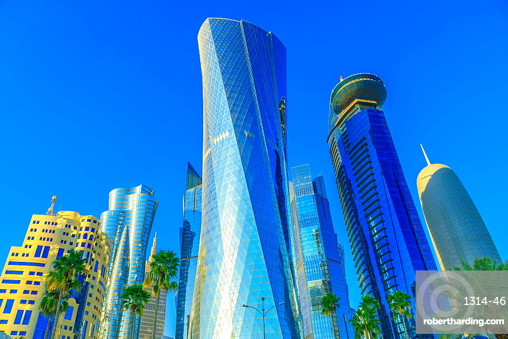 Doha, Qatar - February 17, 2019: bottom view of Al Fardan Towers complex and Doha Tower, iconic glassed high rises in West Bay. Skyscrapers of Financial District in Middle East at sunset light.
