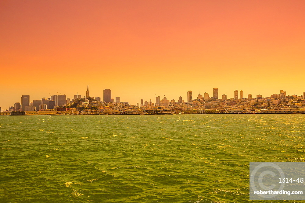 Sea view from boat to Alcatraz at sunset of San Francisco Financial District skyline in California, United States. Copy space.