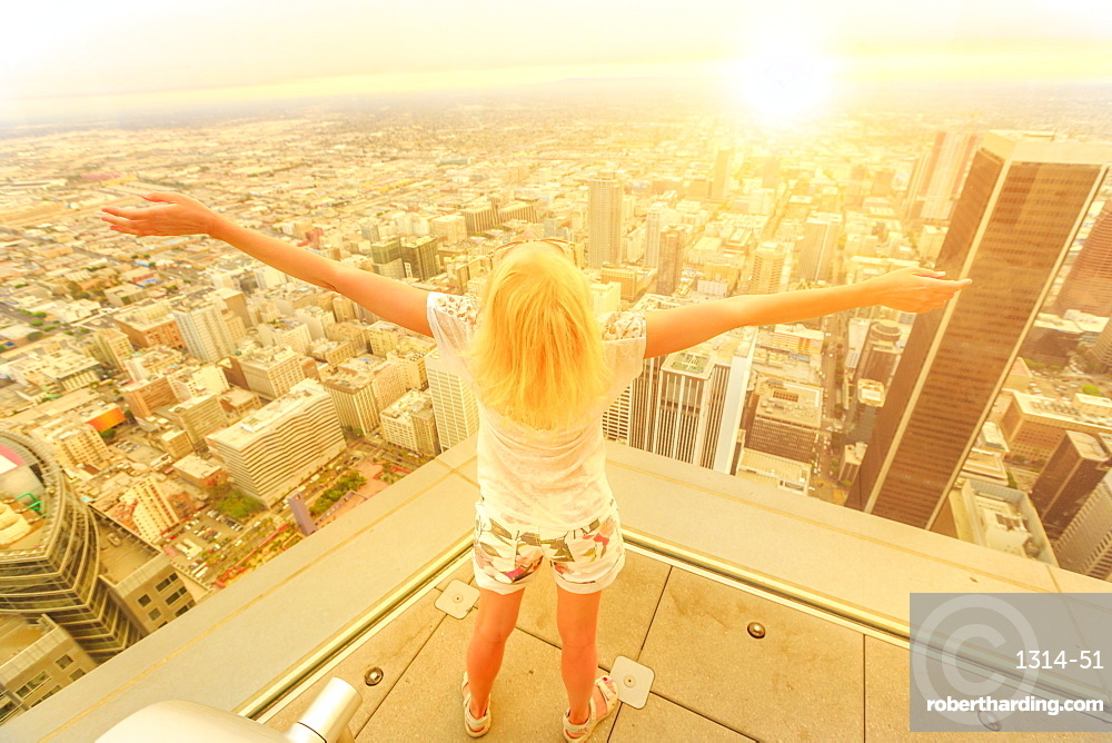 Blonde tourist woman looking at Downtown area of Los Angeles cityscape from observation deck at sunset, Los Angeles, California, United States of America, North America