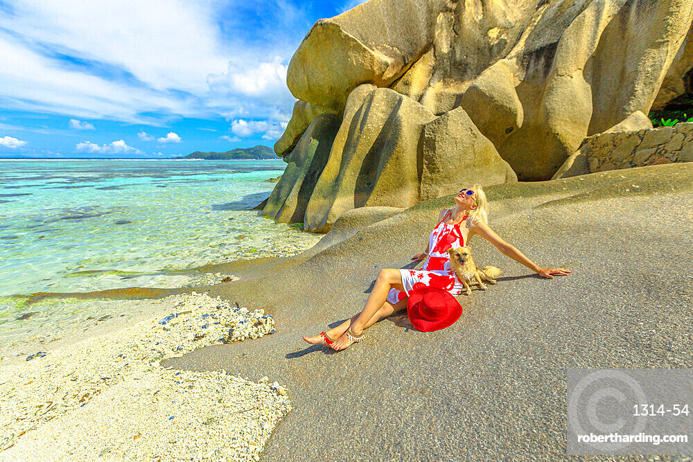 Low tide, crystal sea and granite rocks at Anse Source d'Argent one of the most beautiful beaches in La Digue, Seychelles. Elegant lifestyle tourist woman touches a cute dog sitting on big boulders.