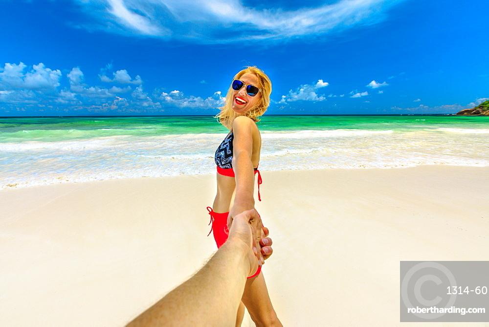 Follow me. Happy tourist woman in bikini holding hand of her partner at Seychelles, Indian Ocean. Beautiful pristine beach, turquoise sea. Wild Anse Kerlan, southwest Praslin. Tropical summer holidays