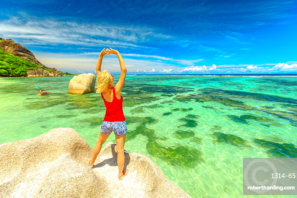 Tourist woman with raised arms in red dress standing on a huge boulder at Anse Source d'Argent. Caucasian female enjoying turquoise sea of La Digue, Seychelles. Scenary landscape of tropical beach.