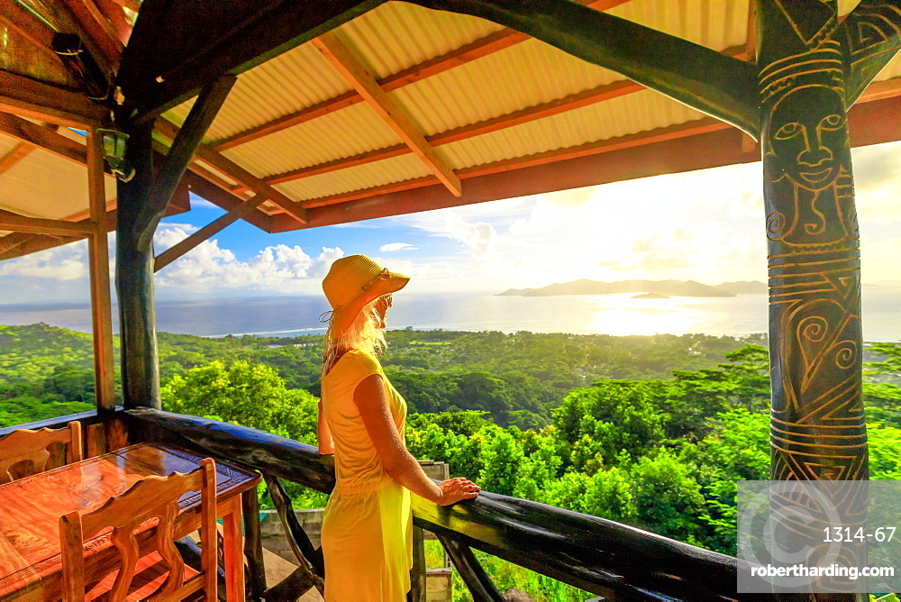 Tourist woman in yellow dress looks towards Praslin Island and La Digue panorama from highest point of island at sunset, La Digue, Seychelles, Indian Ocean, Africa