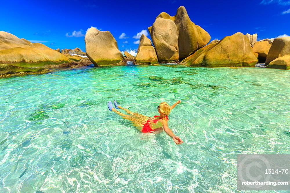 Happy woman in bikini lying in turquoise water in the natural pool of Seychelles beach, Anse Marron, La Digue, Seychelles, Indian Ocean, Africa