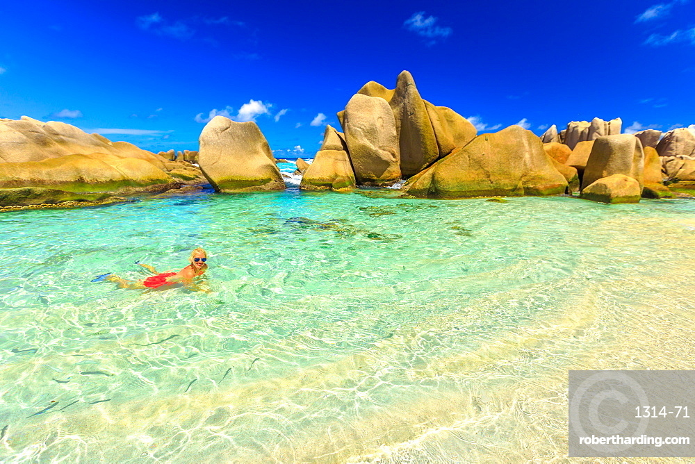 Attractive woman in bikini, in crystal water of natural swimming pool at secret beach, Anse Marron, La Digue, Seychelles, Indian Ocean, Africa