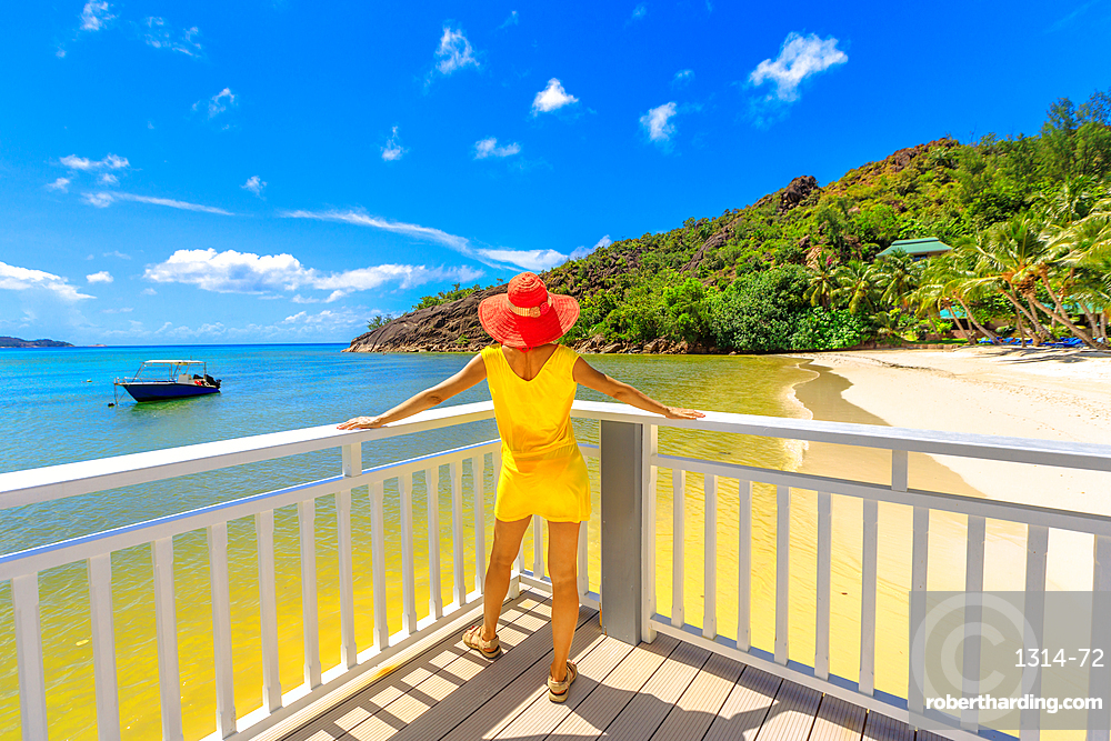 Lifestyle woman in yellow dress at balcony of wooden jetty, looking pristine white beach of Anse Gouvernement in Praslin, Seychelles near Cote d'Or Bay. Elegant tourist in tropical luxury destination.
