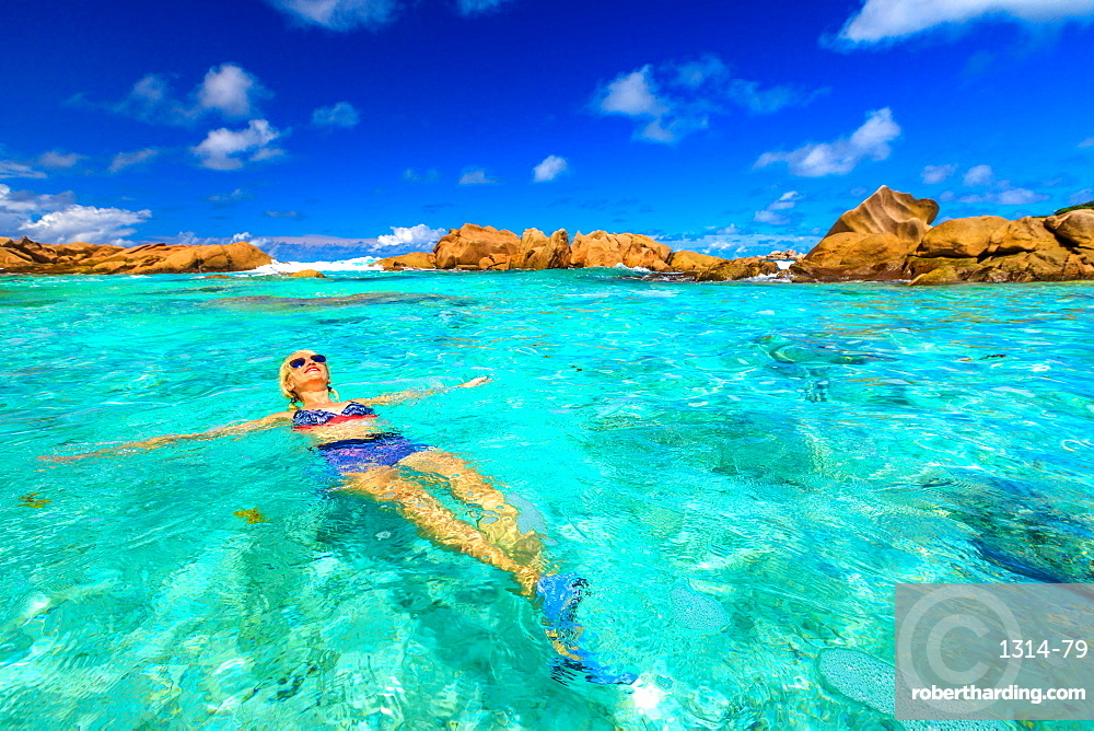 Swimming pool at Anse Cocos with woman in bikini lying in turquoise water of natural pool at Anse Cocos Beach protected by rock formations, La Digue, Seychelles, Indian Ocean, Africa