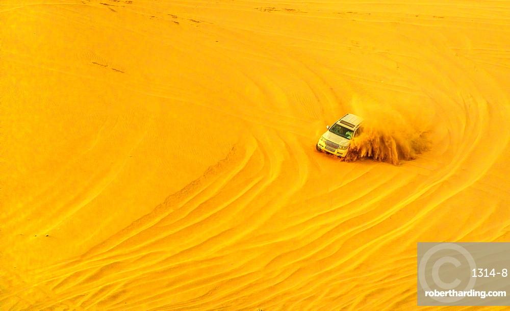 Desert safari adventure. 4x4 vehicle bashing side to side through the desert dunes at sunset in Qatar and Saudi Arabia.