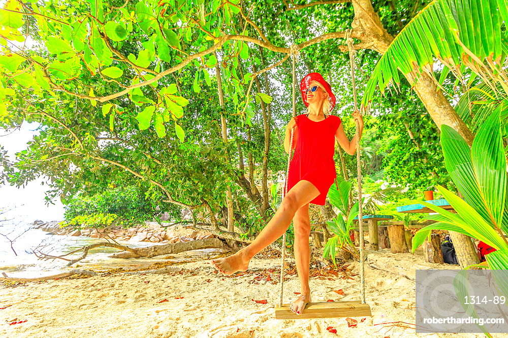Tourist woman in red dress swinging on tropical beach under coconut palm trees of Anse Severe, La Digue, Seychelles, Indian Ocean, Africa