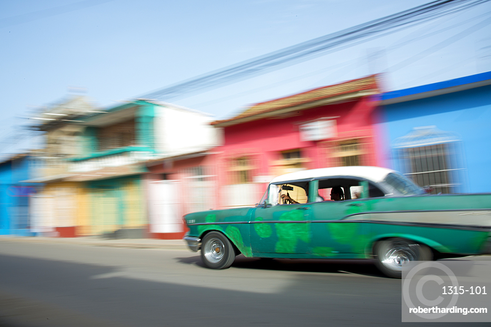 Old car blurring by on the streets of Trinidad, Cuba, West Indies, Caribbean, Central America
