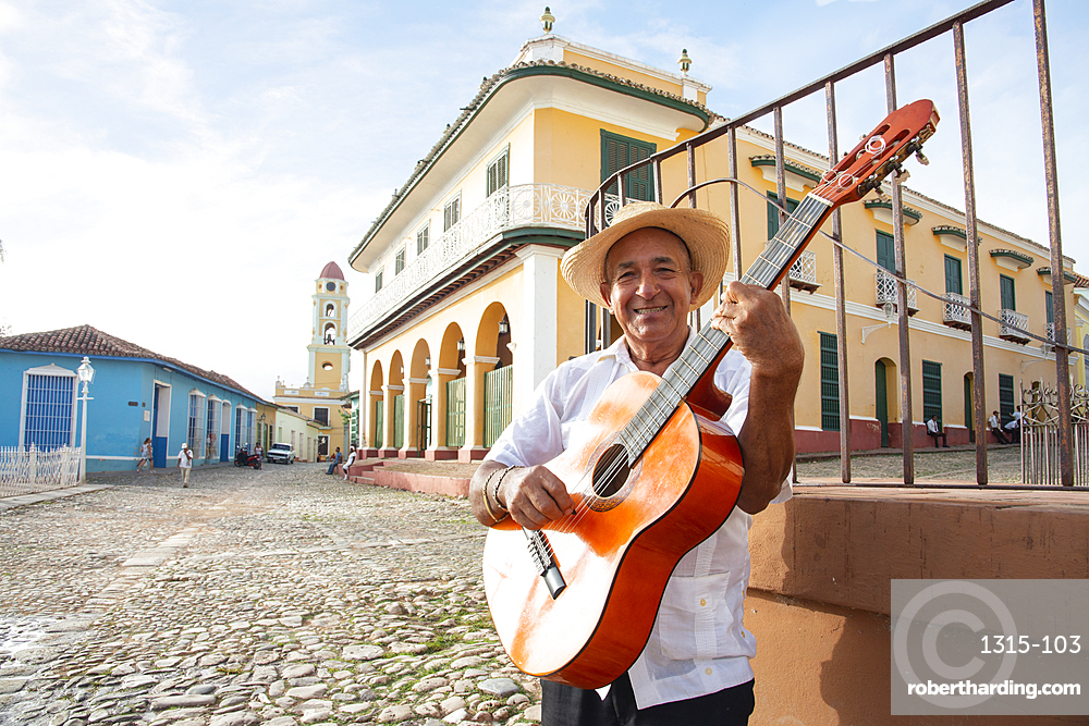 Local man singing and playing his guitar in the Plaza Mayor of Trinidad, Cuba in late afternoon. Model released