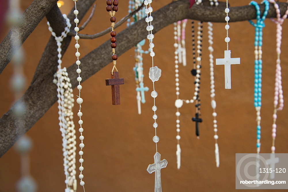 Rosaries left by worshippers, hanging from a tree outside a church in Santa Fe, New Mexico, United States of America, North America