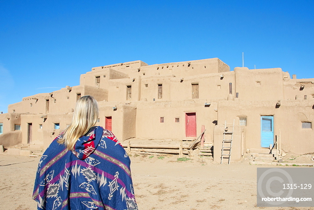 Woman standing in front of Taos Pueblo, Taos, New Mexico. Model released