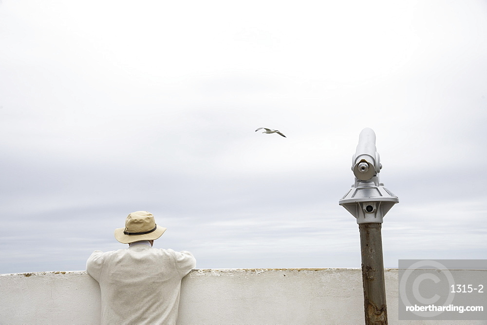 Man peering over a wall beside a telescope along the Algarve coast of southern Portugal.
