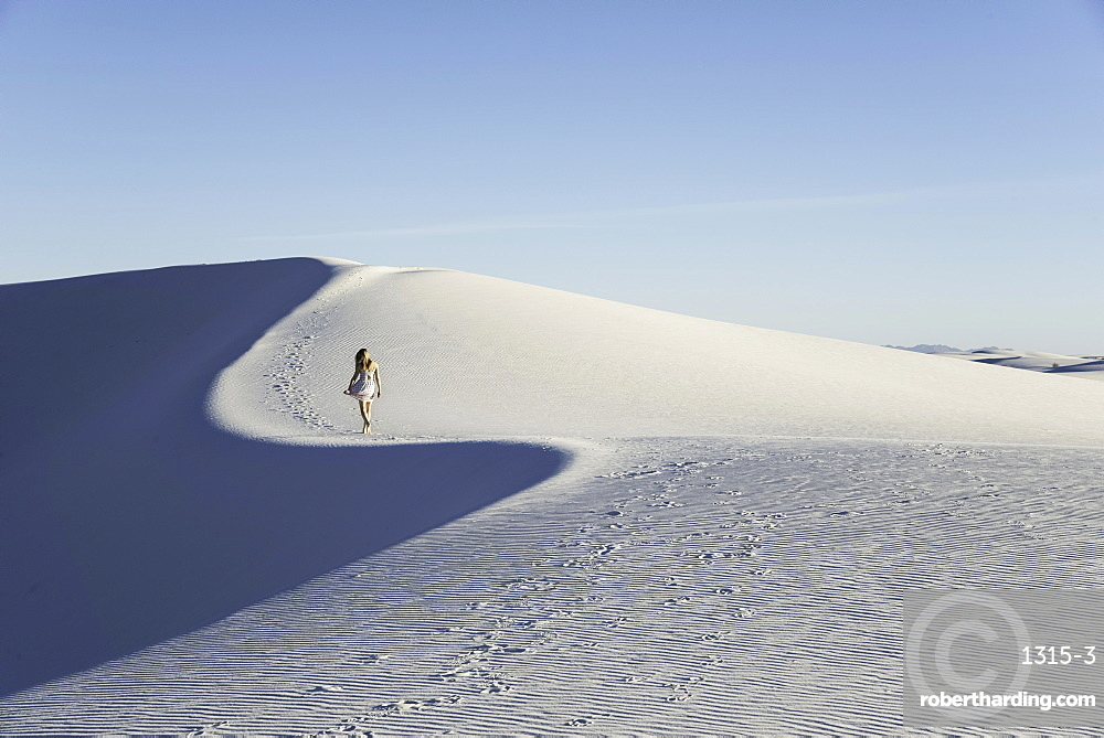 Woman walking along a white sand dune, cast in blue late-afternoon light, in White Sands National Monument, New Mexico, USA.