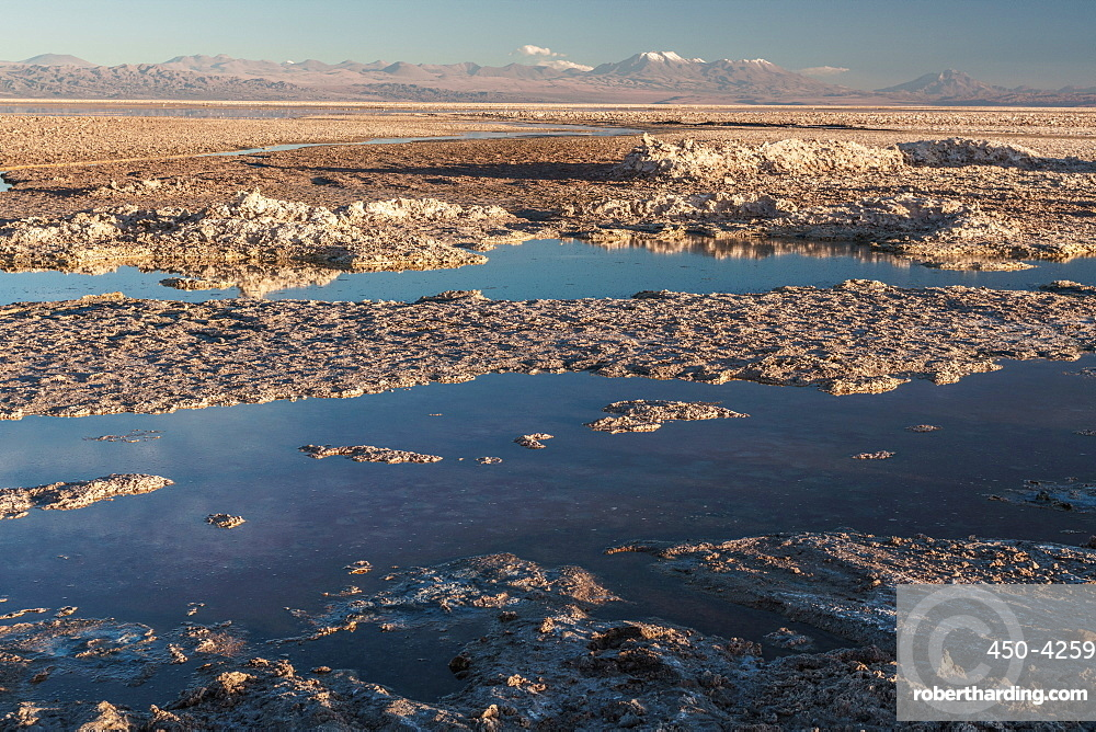 Salt residue piled up by Laguna Chaxa, Atacama Salt Flats, with snow-capped volcanoes, near San Pedro de Atacama, Chile, South America