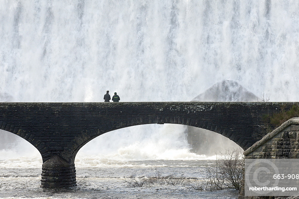 Elan Valley, Powys, Wales, UK. Visitors walk across a bridge as water cascades over the Caban-coch dam, at Elan Valley village near Rhayader in Powys, Wales, UK.