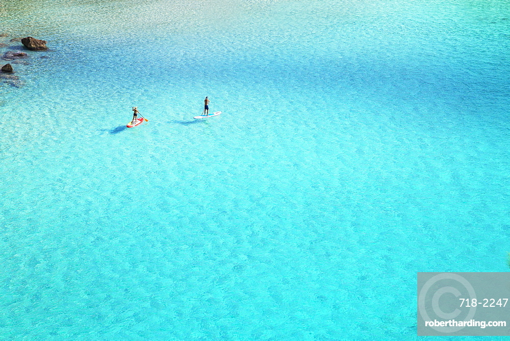 People paddleboarding on the emerald waters of Cala Mitjana, Menorca, Balearic Islands, Spain, Mediterranean, Europe