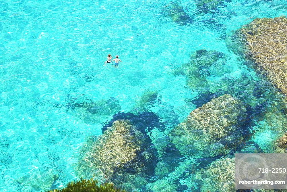 People swimming in the emerald waters of Cala Mitjana, Menorca; Balearic Islands; Spain; Europe