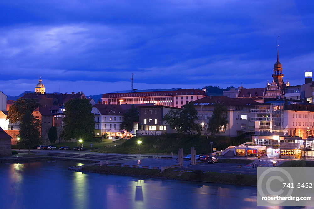 A cityscape of Maribor along the Draca River at night, Slovenia, Europe