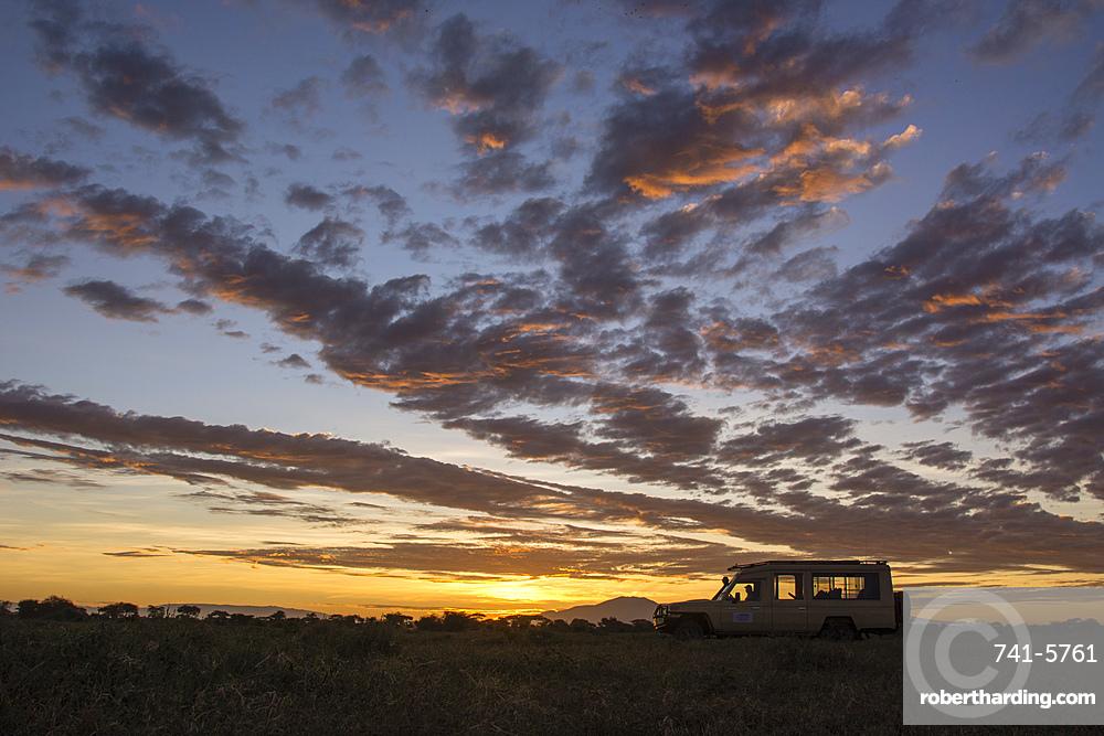 A safari vehicle at sunrise in Ndutu.
