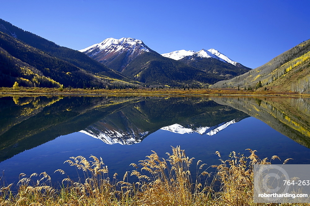 Snow-capped Red Mountain reflected in Crystal Lake with fall colors, near Ouray, Colorado, United States of America, North America