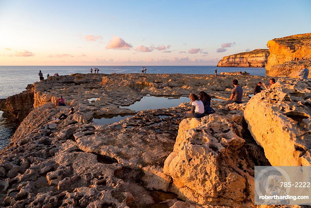 People enjoying sunset at Dwejra Bay on the rugged Gozo coast, Malta, Mediterranean, Europe
