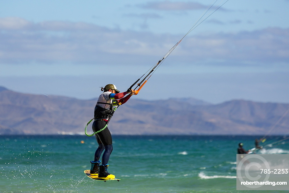 Man jumping whilst kiteboarding off the Playa de La Barca, Costa Calma, on the volcanic island of Fuerteventura, Canary Islands, Spain, Atlantic, Europe