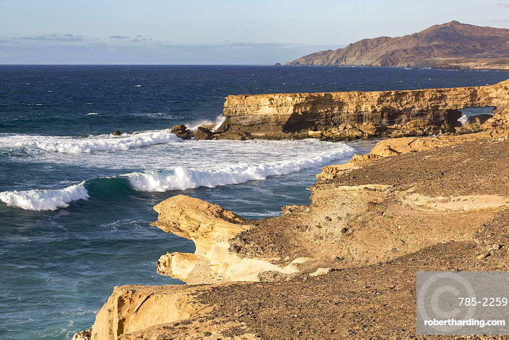 Surf and natural arch on Playa La Pared on the volcanic Canaries island of Fuerteventura