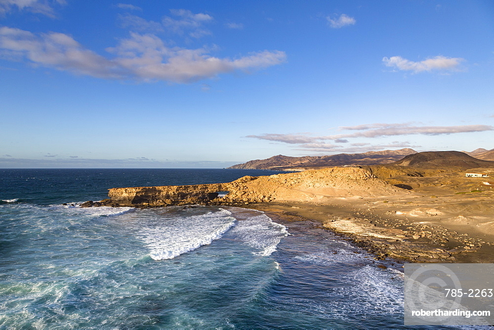 Surf and natural arch on Playa La Pared on the volcanic island of Fuerteventura, Canary Islands, Spain, Atlantic, Europe