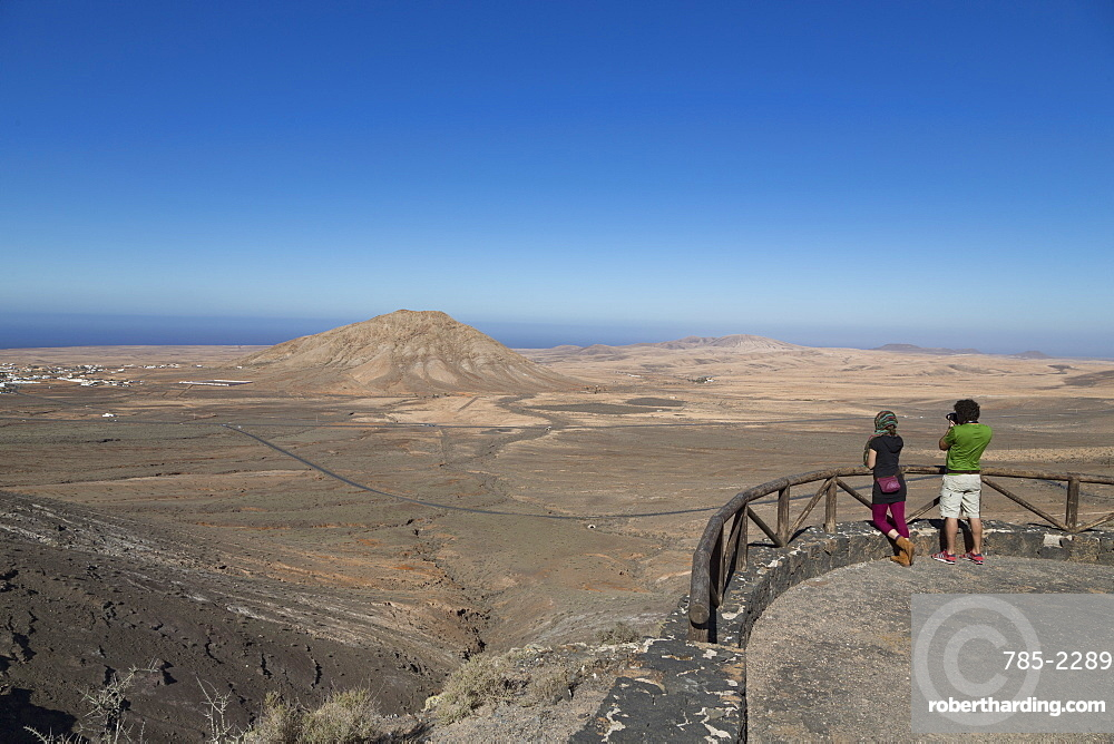 Two people at Mirador de Vallebron looking towards Tindaya volcano on the Canaries island of Fuerteventura