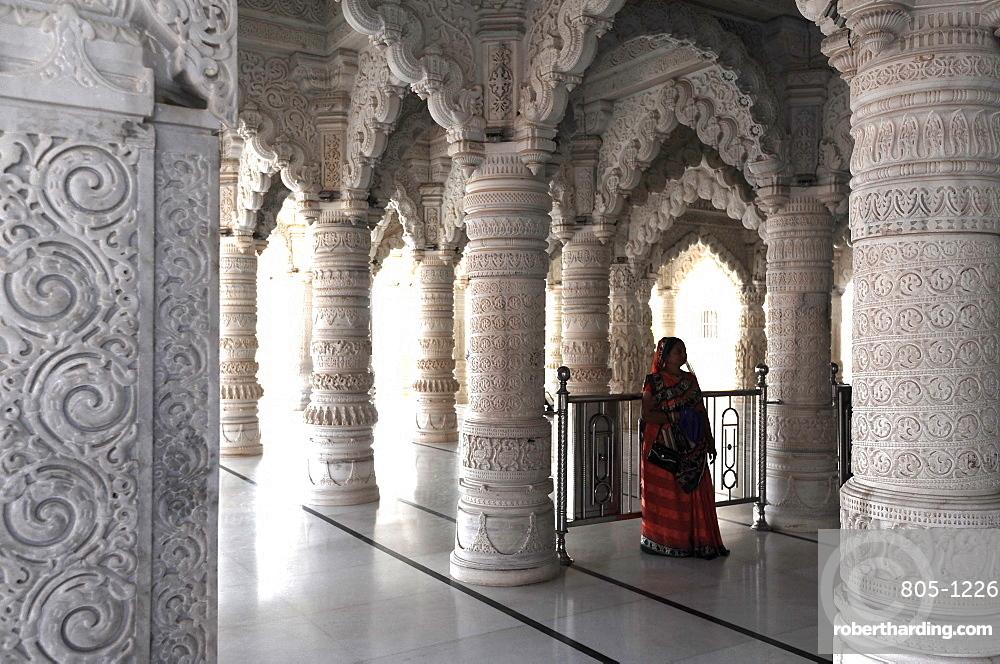 Hindu woman in red sari inside the ornate white marble Swaminarayan Temple, built following the 2001 earthquake, Bhuj, Gujarat, India, Asia