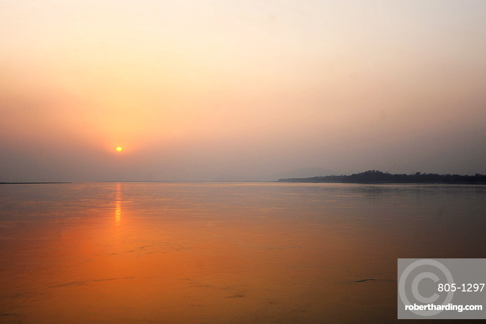 Sun setting over the vast waters of the mighty Brahmaputra river, Assam