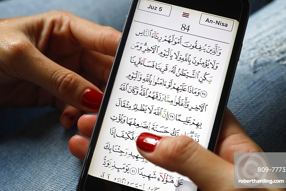Young Muslim woman reading a digital Quran on a smartphone, Vietnam, Southeast Asia, Asia